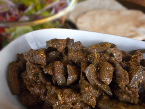 A close up of a plate of food, with beef liver and spices