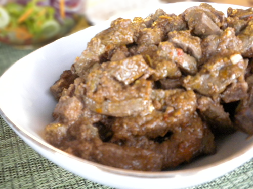 A close up of a bowl of food, with Liver and Sauce