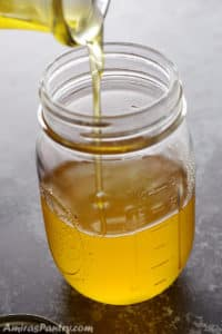 Pouring ghee into a mason jar with the lid on the side.