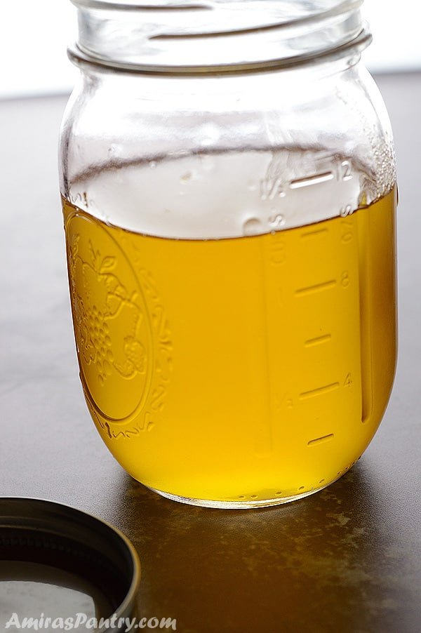 A mason jar with melted clear ghee in it.