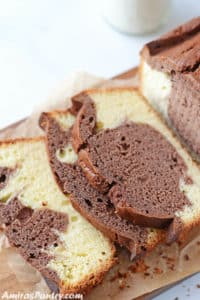 A loaf of marble cake on a wooden cutting board with half of it slices on the board with a milk bottle in the back.