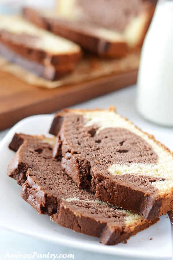 Two pieces or marble cake on a white plate with a bottle of milk and a cutting board on the back.