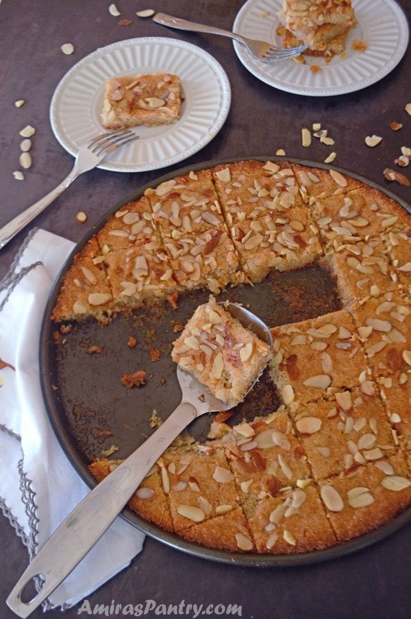 Basbousa is a delicious farina, yogurt and coconut cake. Decorated with nuts and drizzled with simple syrup.