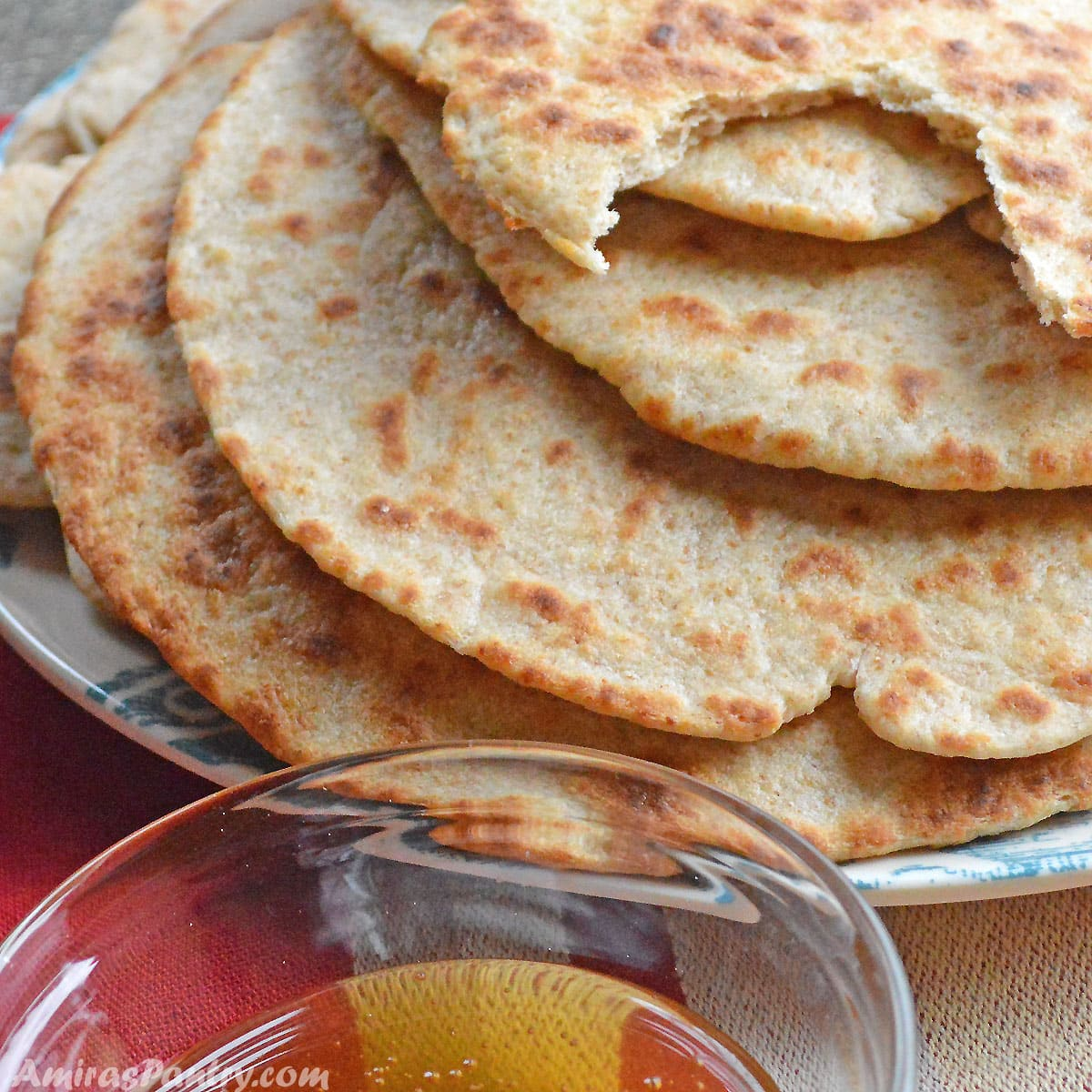 A stack of flatbread on a blue plate with a small bowl of honey.