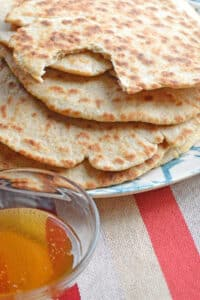 Skillet flatbread with a cut and small bowl of honey