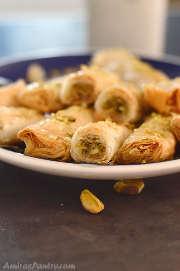 A close up of a plate of food, with Baklava rolls
