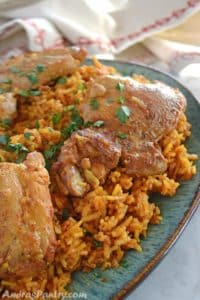 Rice on a big serving platter topped with chicken and garnished with parsley.