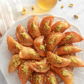 A plate of food on a table, with Qatayef