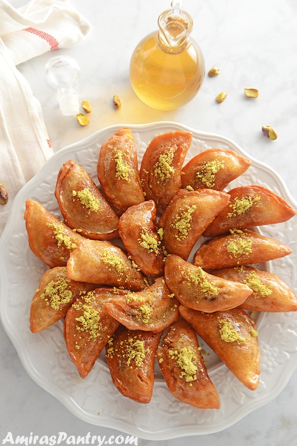 A white platter with qatayef garnished with ground pistachios and a bottle of syrup right next to it.