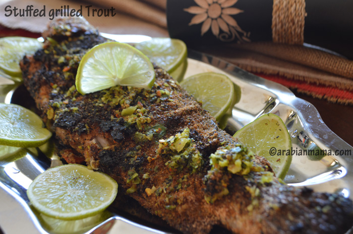 A plate of food on a table, with grilled Trout and lemons