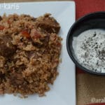 A close up of a plate of food with rice and meat, cup of yogurt dip