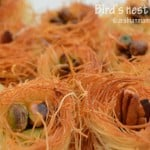 A close up of knafeh like bird's nest with nuts