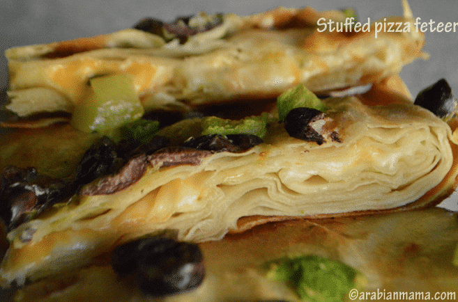 A close up of a pizza fetter with olives and cheese