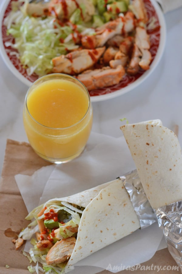 Two chicken wraps on top of each other with a glass of juice and another plate with garlic chicken on it.
