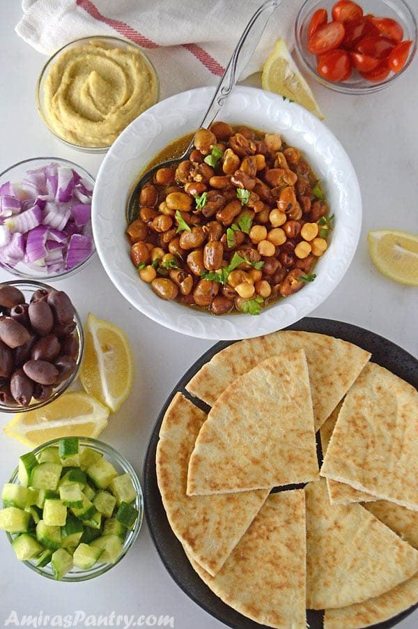 A breakfast table with a white bowl filled with fava beans with other plates of pita bread, onion, black olives and diced cucumber.