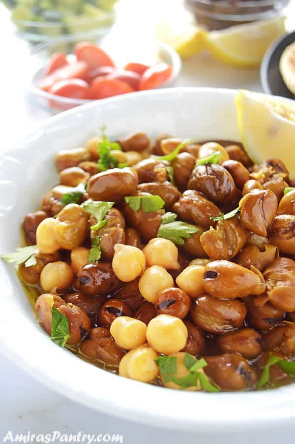 A white bowl with ful medames mixed with chickpeas with lemon wedges on the side.
