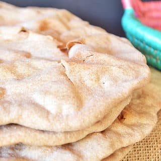 A stack of unleavened flat bread with a burlap underneath.