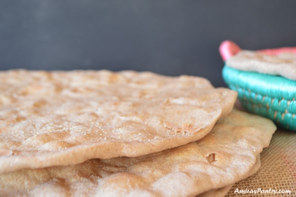 A stack of unleavened flat bread with a bamboo plate on the back
