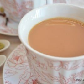 A cup of spiced tea on a plate