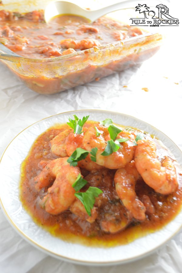 A plate with shrimp in minty tomato sauce with a big baking dish in the back