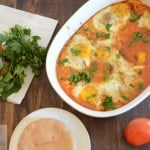 A bowl of food on a table, with Shakshouka and bread