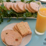 A plate with a cut chicken roll slices and olives, a cup of orange juice