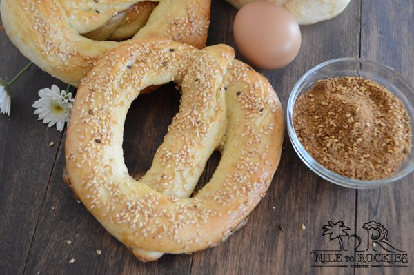 A Simit bread sitting on top of a wooden table with spiced and egg