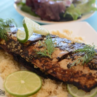 A plate of food, with Tamarind grilled fish and lemons
