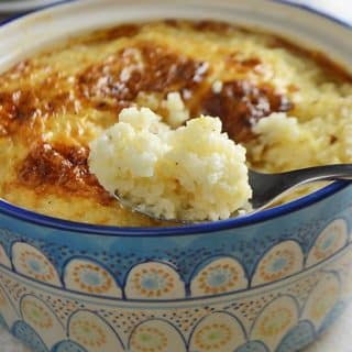 A close up of a bowl of food, with Rice pudding and spoon