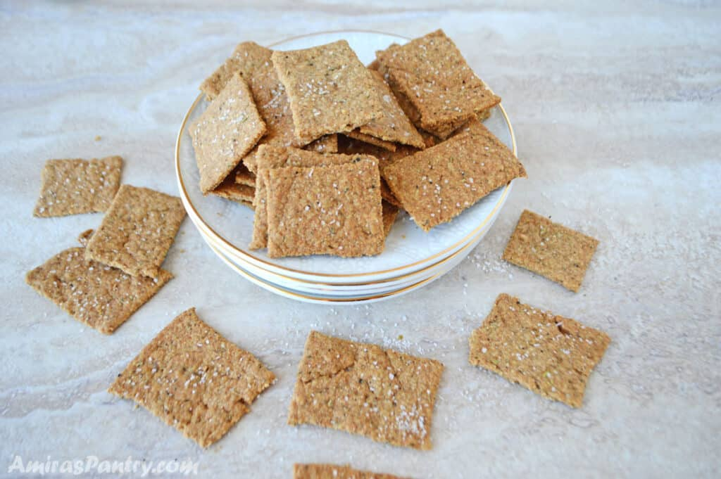 homemade flatbread crackers piled up on a white plate on a marble table