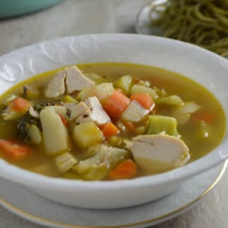 A bowl of soup, with chicken and vegetables