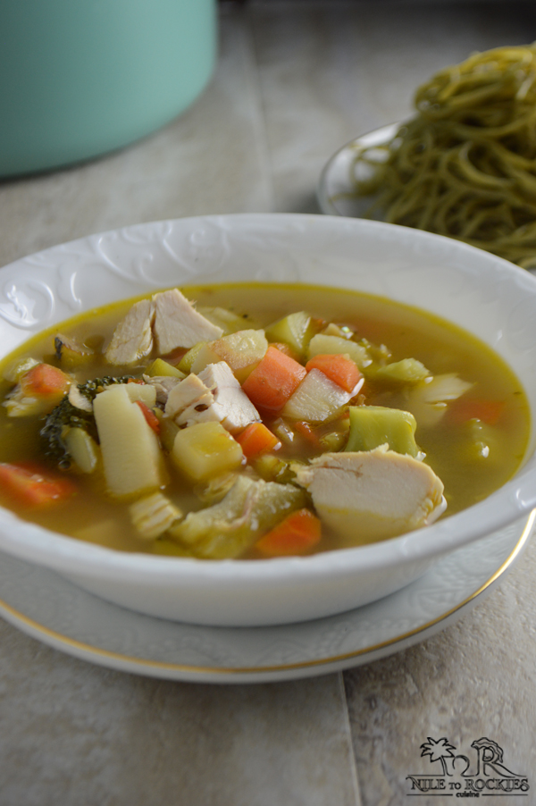 A bowl of soup on a plate, with chicken and vegetables