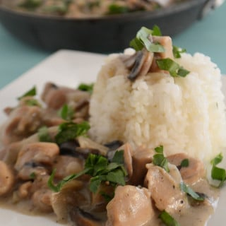A bowl of food on a plate, with Chicken, Rice and Mushroom