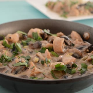 A bowl of food on a plate, with Chicken and Mushroom