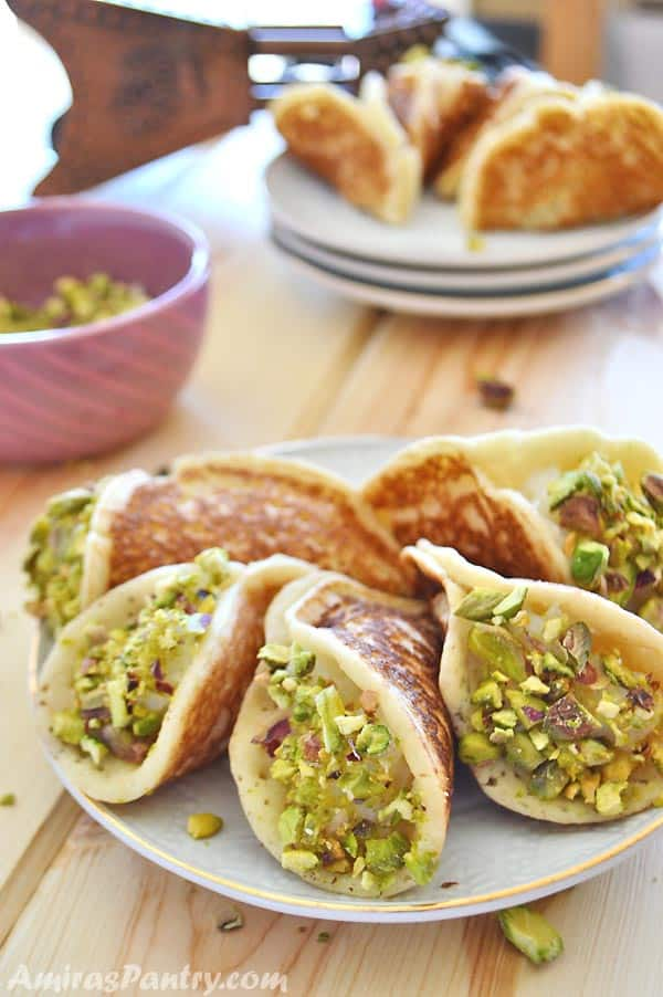 A white plate filled with qatayef stuffed with cream with a small bowl of cracked pistachios in the back.