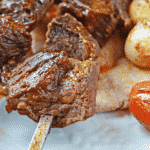 A close up of beef skewer on a pita bread