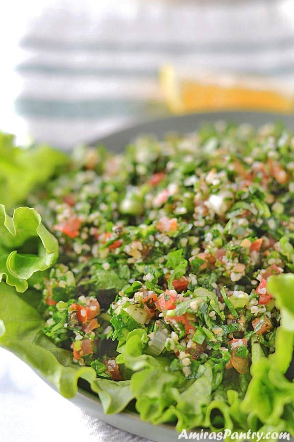 A green plate with tabouli served over lettuce leaves.
