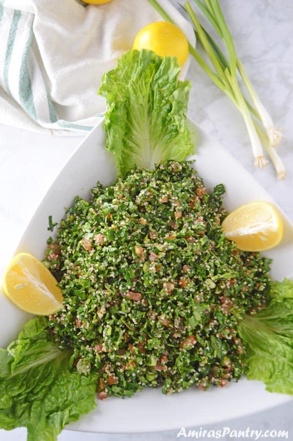 A big bowl of tabouli served with Romaine lettuce and lemon wedges.