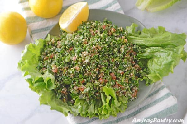 Tabbouleh served in a green plate with lettuce and lemon wedges.