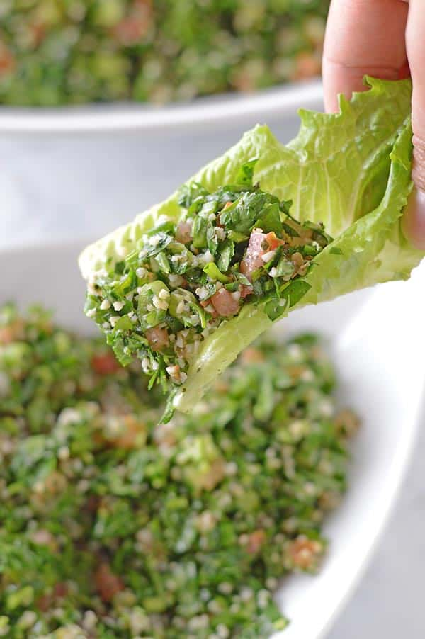 A hand scooping some tabbouleh salad with lettuce.