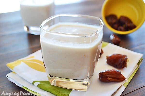 A cup of healthy date shake with some dates on a white and green napkin with another cup in the back.