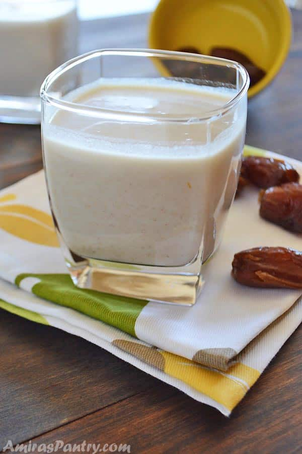 A cup of healthy date shake with some dates on a white and green napkin