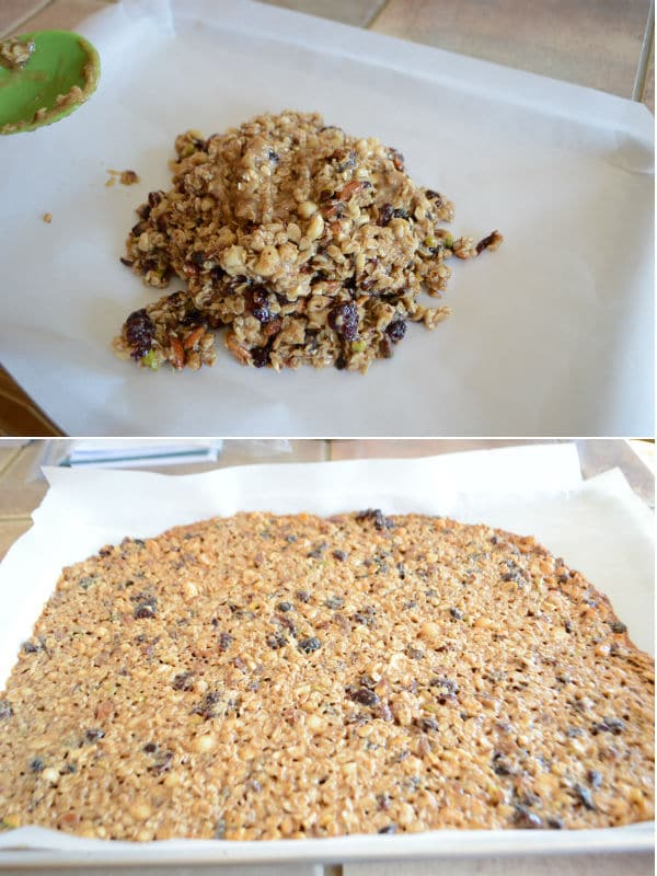 Granola mixture is spread in a baking sheet and getting ready to put in the oven.