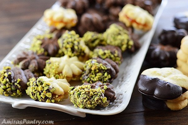 A white platter with butter cookies glued with jam and dipped in chocolate with some pistachios on the top.