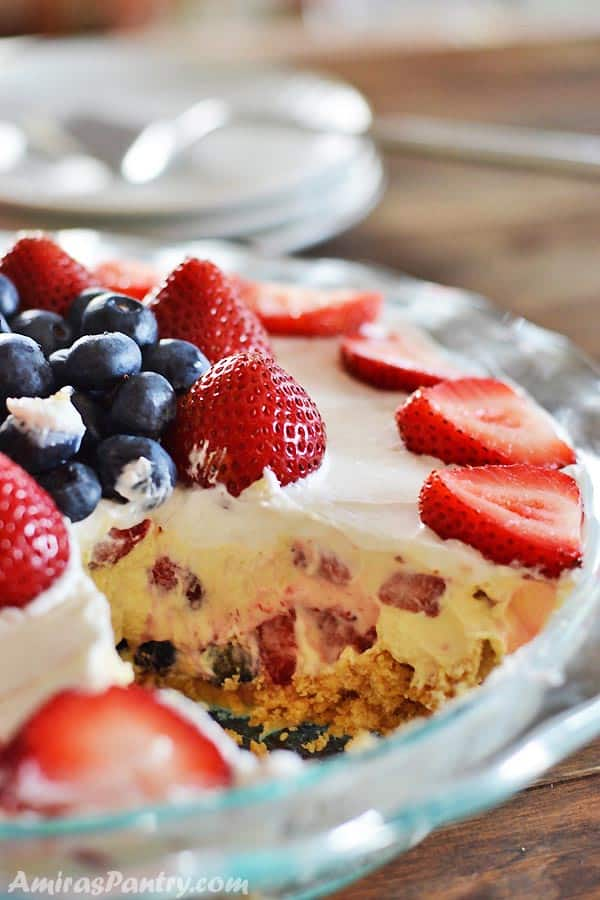A close up of a cake with fruit in a glass bowl on top of a table