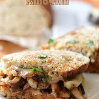 A close up of a sandwich on a plate, with Cheese and Eggplant