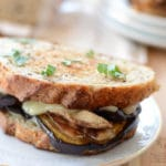 A sandwich on a plate, with Cheese and Eggplant