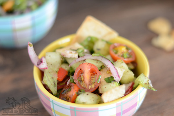 A small serving bowl of fattoush salad with another serving bowl at the background.