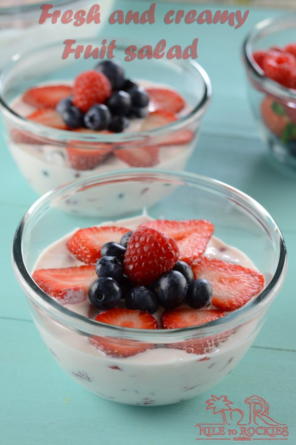 A bowl of fruit on a table, with Cream and Salad
