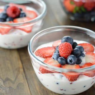 A bowl of fruit on a plate, with Cream and Salad